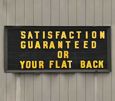 Outdoor sign with text: SATISFACTION GARANTEED OR YOUR FLAT BACK