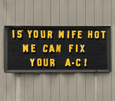 Outdoor sign with text: IS YOUR WIFE HOT - WE CAN FIX YOUR A.C!