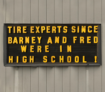 Outdoor sign with text: TIRE EXPERTS SINCE BARNEY AND FRED WERE IN HIGH SCHOOL!
